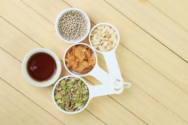 Sfondo di erbe tailandesi con pepe, citronella, aglio, zucchero di cocco e salsa di pesce Foto Premium