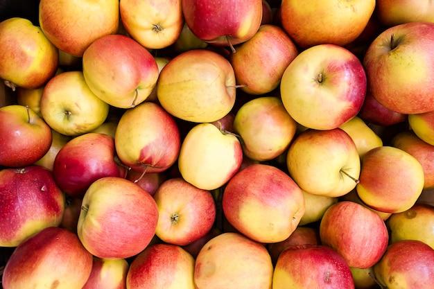 Sfondo di mele rosse e gialle. varietà di mele fresche coltivate nel negozio. Foto Premium