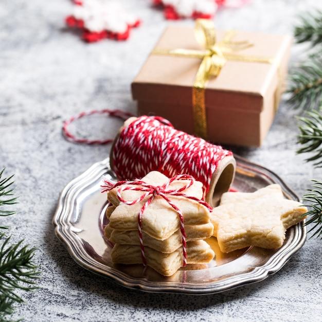 Sfondo di natale. biscotto di panpepato festivo con nastro, rami di pino Foto Premium