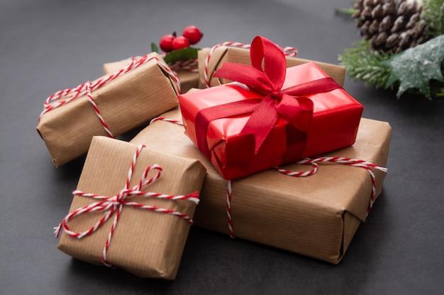 Sfondo di natale con scatole regalo, rami di abete e pigne. vacanze invernali. Foto Premium