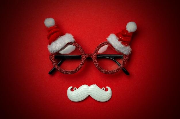 Sfondo di natale rosso con occhiali santa e baffi bianchi hipster. Foto Premium