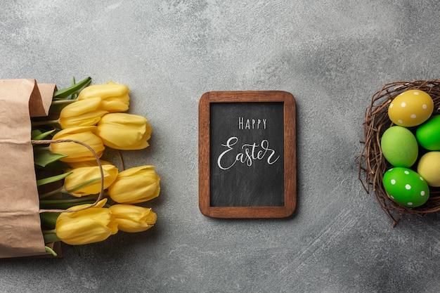 Sfondo di pasqua con uova colorate e tulipani gialli su grigio pietra. vista dall'alto con lo spazio della copia. Foto Premium
