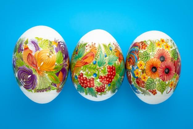 Sfondo di pasqua uova pasquali colorate con ornamento su sfondo blu. evento festivo stagione primaverile. carta regalo, concetto di tradizione cristiana. Foto Premium