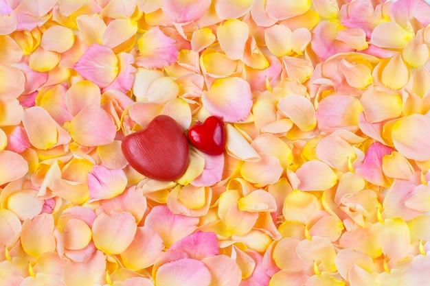 Sfondo di petali di rosa rosa e due cuori rossi Foto Premium