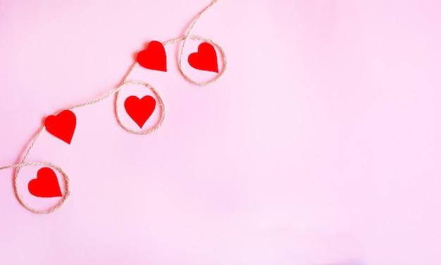 Sfondo di san valentino con cuori rossi e accessori su sfondo rosa. sfondo di forme d'amore. Foto Premium