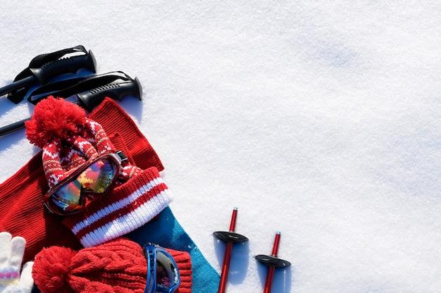 Sfondo di sport invernali neve con bastoncini da sci, occhiali, cappelli e guanti con copyspace. Foto Gratuite