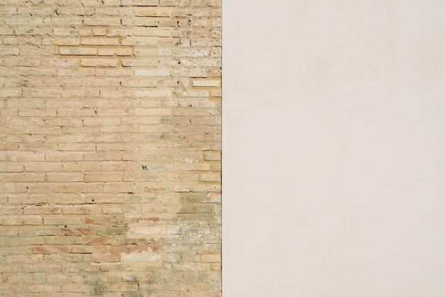 Sfondo di un muro metà bianco e metà con mattoni, diviso in due metà. Foto Premium