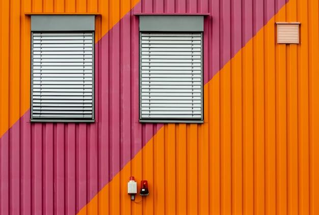 Sfondo di una parete di metallo arancione e viola con tapparelle bianche Foto Gratuite