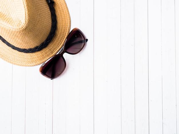 Sfondo estivo cappello di paglia bracciali sandali occhiali da sole seashells su un tavolo blu Foto Premium