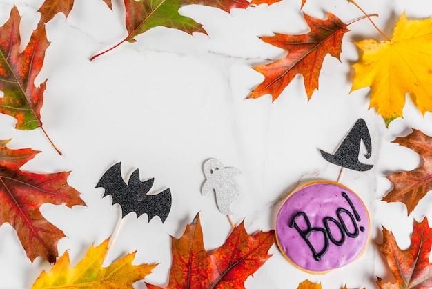 Sfondo festivo per halloween, tavolo in marmo bianco con biscotto di pan di zenzero con la scritta boo !, simboli di festa (pipistrello, cappello da strega, fantasma) e foglie gialle rosse autunnali, vista dall'alto copia spazio cornice Foto Premium