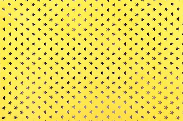 Sfondo giallo da carta stagnola con stelle dorate Foto Premium