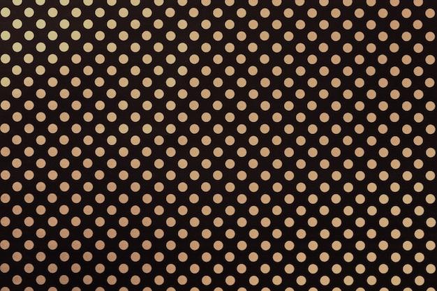 Sfondo nero da carta da imballaggio con un modello di primo piano dorato a pois. Foto Premium
