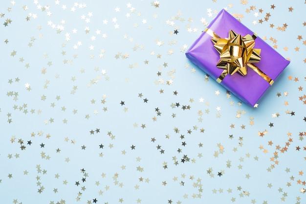 Sfondo piatto laico per la celebrazione di natale e capodanno. le scatole regalo sono viola con fiocchi di nastri d'oro e stelle di coriandoli su sfondo blu. vista dall'alto copia spazio. Foto Premium