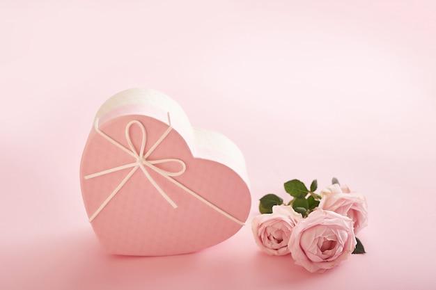 Sfondo rosa con fiori e scatola regalo Foto Premium