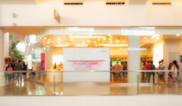 Sfondo sfocato centro commerciale. persone che camminano e fanno shopping in vacanza Foto Premium