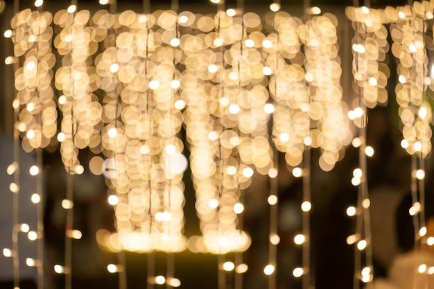 Sfondo sfocato di molte piccole decorazioni di lampadina nella festa di notte. Foto Premium