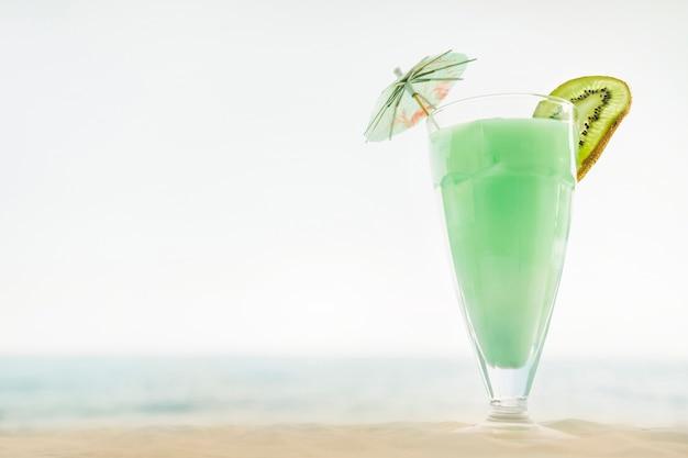 Sfondo spiaggia con cocktail di kiwi Foto Gratuite