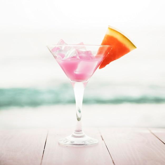 Sfondo spiaggia con cocktail rosa e anguria Foto Gratuite
