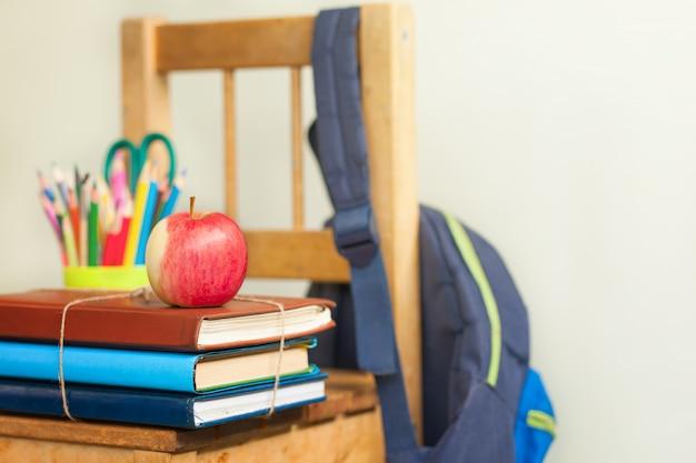 Sfondo torna a scuola con una pila di libri e mela rossa. Foto Premium