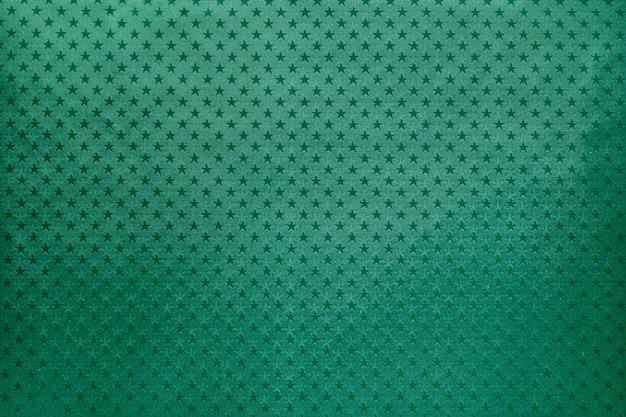 Sfondo verde da carta stagnola con un motivo a stelle Foto Premium