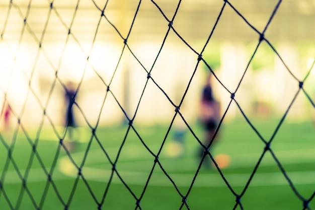 Sfuocatura della rete di addestramento di calcio sulla terra di addestramento con i bambini Foto Premium