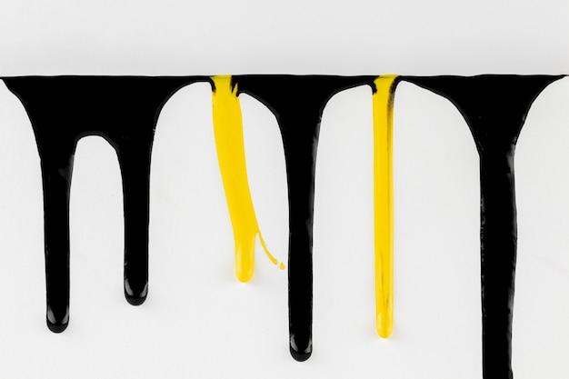 Sgocciolatura nera e gialla della pittura sul fondo bianco Foto Gratuite