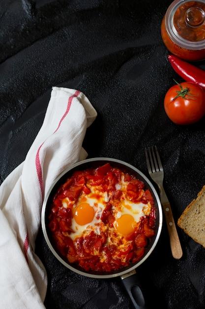 Shakshouka o shakshuka, uova in salsa di pomodori e peperoni, vista dall'alto Foto Premium