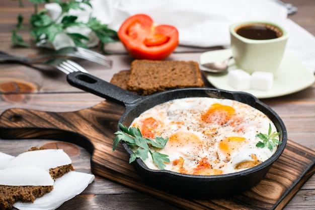 Shakshuka di uova fritte con pomodori e prezzemolo in una padella, pane con burro e caffè Foto Premium