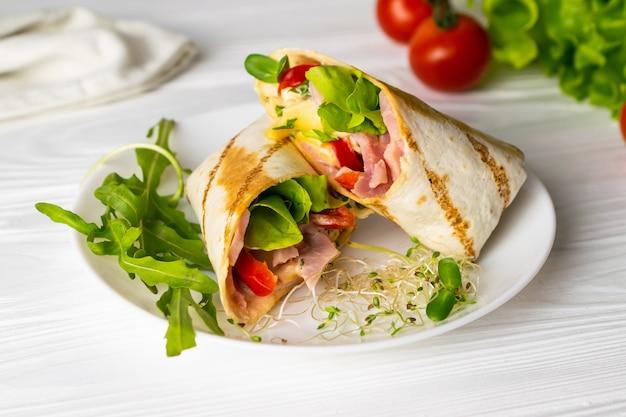 Shaurma ha avvolto il panino con i pomodori e il formaggio dei pomodori della lattuga su un piatto bianco Foto Premium