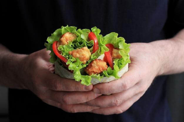 Shawarma in mani maschili. doner kebab. shawarma con carne, cipolle, insalata e pomodoro. Foto Premium