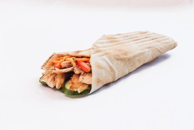 Shawarma isolato con un'ombra. cibo orientale a base di carne di pollo, pomodori, cetrioli nel pane pita Foto Premium