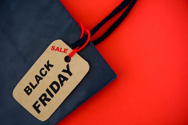 Shopper con sacchetto di carta del black friday e etichetta del biglietto su sfondo rosso. Foto Premium