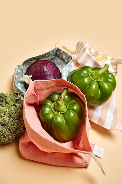 Shopper in stoffa di cotone per generi alimentari con verdure. sfondo beige. niente plastica Foto Premium