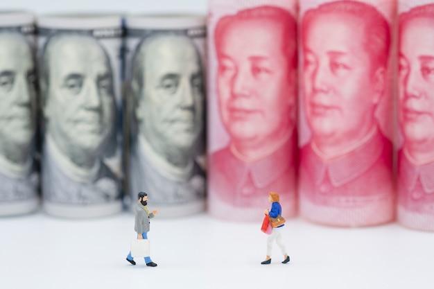 Shopping figure in miniatura con banconote in dollari statunitensi e cinesi yuan. Foto Premium