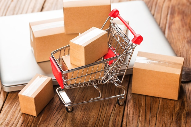 Shopping online a casa concetto. scatole in un carrello sulla tastiera di un computer portatile. Foto Premium