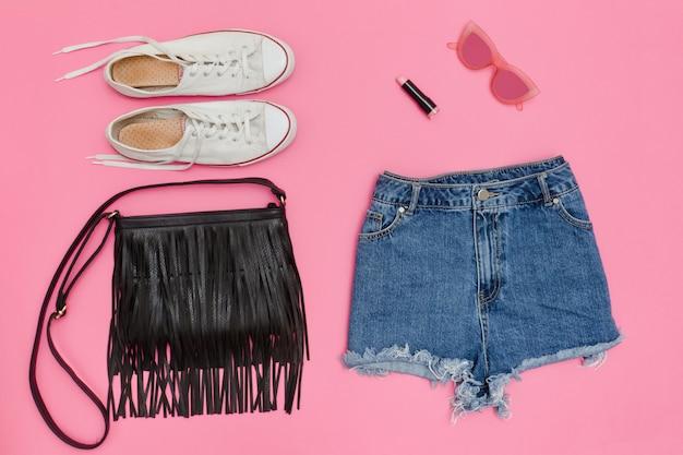Shorts di jeans, scarpe da ginnastica bianche, borsa nera. sfondo rosa brillante. concetto alla moda Foto Premium