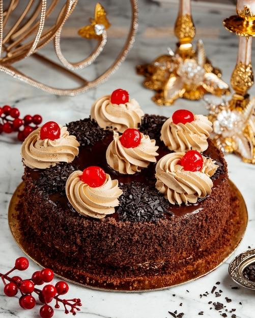 Sideview di torta al cioccolato con panna montata e ciliegie sul tavolo Foto Gratuite
