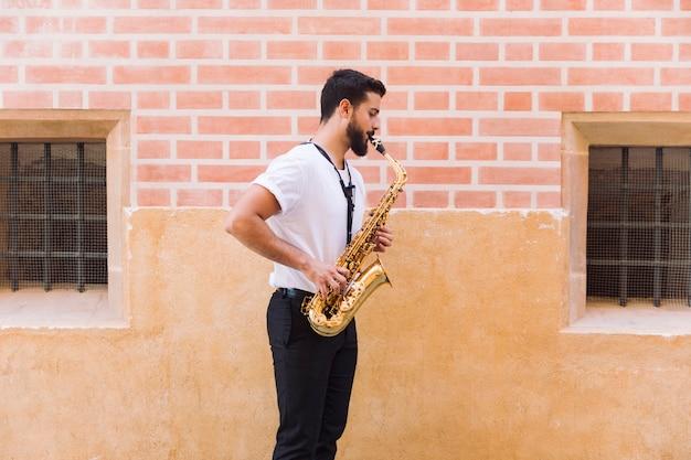 Sideways medium shot uomo che suona il sassofono Foto Gratuite