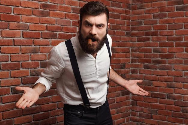 Sigaro di fumo del giovane uomo bello brutale di rabbia sul muro di mattoni. Foto Gratuite