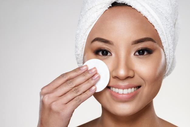 Signora abbastanza allegra con l'asciugamano sulla testa che pulisce il suo fronte Foto Gratuite