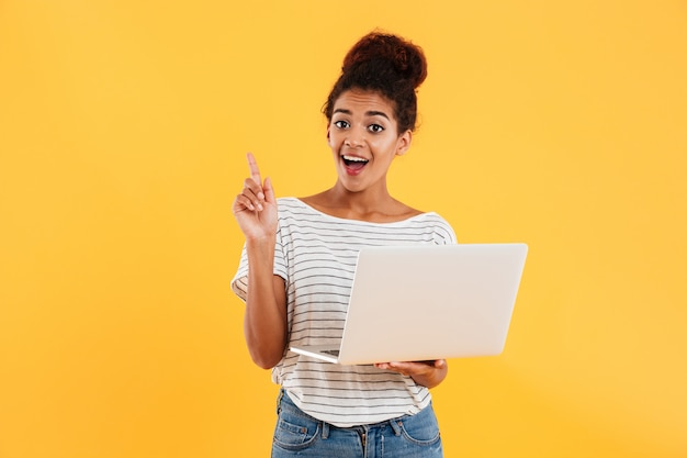 Signora africana abbastanza allegra e computer portatile giudicante isolati Foto Gratuite