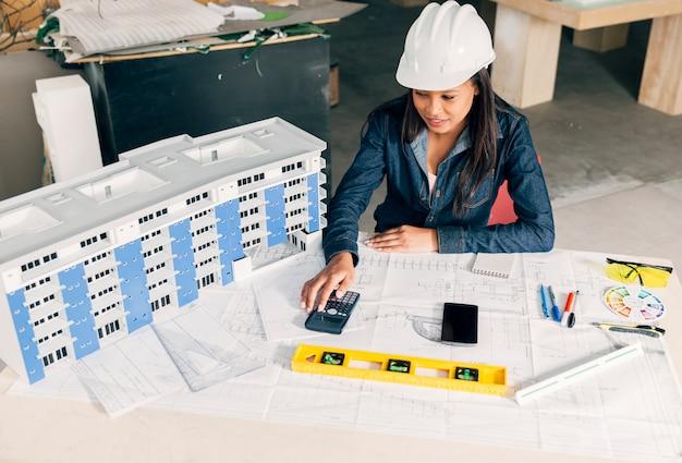 Signora afroamericana in casco di sicurezza che si siede vicino al modello di costruzione Foto Gratuite