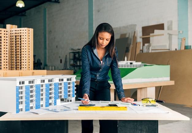 Signora afroamericana seria con la penna che sta modello vicino di costruzione sulla tavola Foto Gratuite