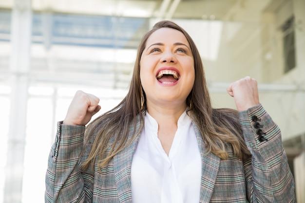 Signora allegra di affari che celebra successo all'aperto Foto Gratuite