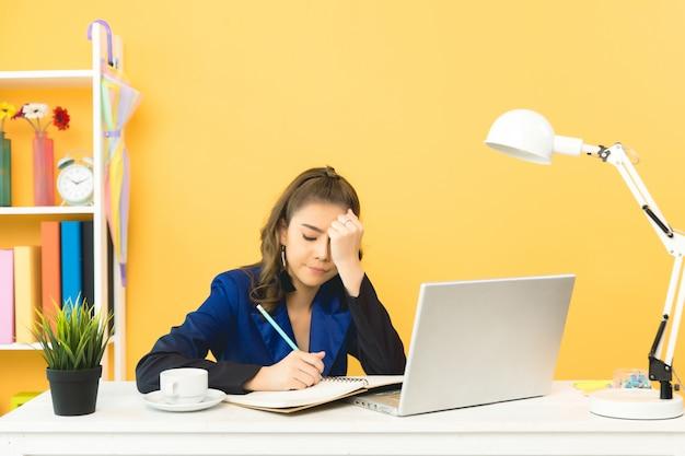 Signora allegra di affari che lavora al computer portatile in ufficio Foto Gratuite