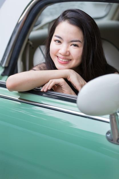 Signora asiatica che sorride in un'automobile dell'annata Foto Premium