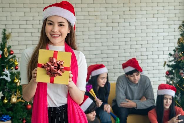 Signora asiatica in un bel vestito con una confezione regalo. carino sorridente. divertirsi festa di natale. vigilia di natale, Foto Premium