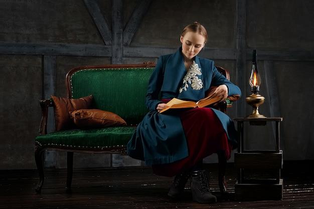 Signora attraente che legge libro antico vicino alla lampada di cherosene d'annata Foto Premium