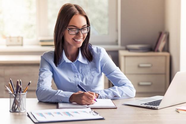 Signora attraente di affari in vestiti ed occhiali convenzionali. Foto Premium