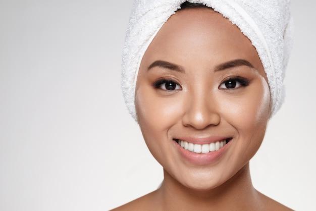 Signora attraente senza trucco con un asciugamano sulla testa che sorride alla macchina fotografica Foto Gratuite